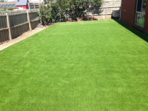 Synthetic Grass Melbourne - Expansive Backyard Grass Lay with Sleeper Retaining Wall